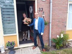 Wethouder reikt bloemen uit aan mantelzorger